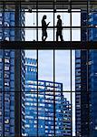 Business people meeting on an elevated walkway between office buildings.