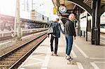 Young man pulling teenage girl on skateboard at railroad station platform