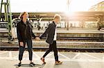 Full length of young man pulling teenage girl on skateboard at railroad station platform