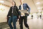 Happy young couple walking in illuminated underground walkway