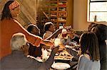 Multi-generation family enjoying Christmas dinner, toasting glasses