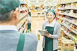 Senior man and woman worker checking stocks at supermarket