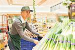 Senior man workers arranging produce at supermarket