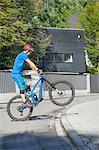 Man doing a wheelie with mountain bike, Bavaria, Germany