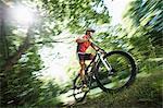 Mountainbiker speeding in forest, Bavaria, Germany