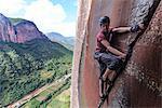 Rock climber climbing sandstone rock, Liming, Yunnan Province, China
