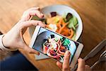 Woman taking photo of vegan meal