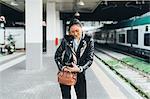 Woman walking along train platform, going through bag, using smartphone