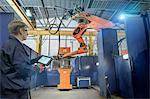 Engineer with controller in robotic welding bay in engineering factory