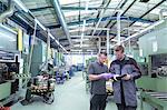 Engineers inspecting pressed metal part in metal pressing factory
