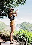 Young female tourist taking smartphone photographs of Victoria Falls, Zimbabwe, Africa