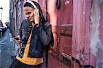 Man in street listening to music through headphones on smartphone