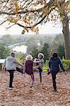 Active seniors stretching, exercising in autumn park