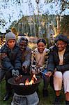 Grandparents and grandchildren roasting hot dogs over campfire