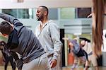 Male instructor helping teenage boy in dance class studio