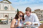 Young couple using mobile phone, Santa Maria Novella Church and Square, Florence, Toscana, Italy