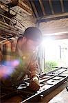 Blacksmith hammering metal on workbench in blacksmiths shop