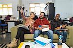 Happy creative business people taking selfie in casual open plan office