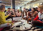 Creative business team meeting, brainstorming in circle on floor
