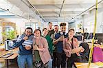 Portrait happy, playful creative business team in open plan office