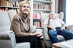 Senior couple sitting on armchairs, portrait.