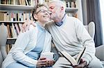 Senior man kissing woman on cheek with arm around her.