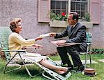 1960s MAN WOMAN SITTING LAWN CHAIRS INSURANCE SALESMAN HANDING CHECK TO WOMAN