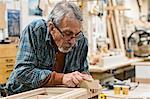 Senior Caucasian  carpenter sanding a wooden cabinet part in a large woodworking shop.