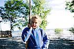 Girl exploring shore with stick, Kingston, Canada