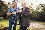 Mature couple drinking coffee and raking autumn leaves in backyard