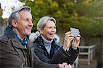 Happy mature couple using camera phone in park