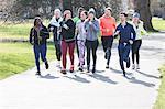 Runner friends running in sunny park