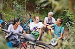 Friends mountain biking, resting in woods