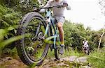 Man mountain biking on muddy trail