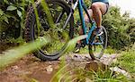 Woman mountain biking on muddy trail