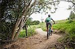 Man mountain biking on rural trail