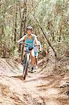 Woman mountain biking on sunny trail in woods