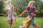Children in costume running in park