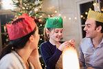 Family in paper crowns enjoying Christmas dinner