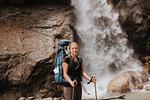 Hiker in front of waterfall, Annapurna Circuit, the Himalayas, Manang, Nepal