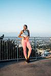 Woman leaning against railings on hilltop, Los Angeles, US