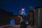 Climber reading book on rock climbing route, Canyonlands National Park, Moab, Utah, USA