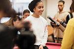 Smiling teenage girl being interviewed for vlog