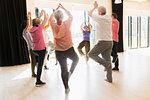 Active seniors exercising, practice yoga tree pose in circle