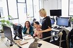Businesswomen working at computer in open plan office