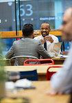 Businessmen talking, working in cafe