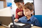 Focused boys using laptop