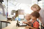 Teacher and schoolgirls using laptop in science center