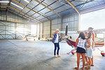 Pilot talking to friends at prop airplane in airplane hangar