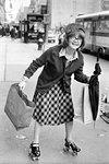 1970s CHARACTER SHOPPING BAG LADY WEARING ROLLER SKATES CARRYING UMBRELLA AND BAGS FUNNY FACIAL EXPRESSION LOOKING AT CAMERA